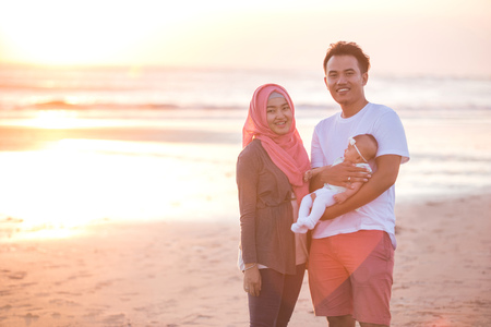 muslim baby girl: portrait of happy parent with newborn baby at the beach having fun together Stock Photo