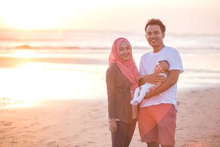 retrato de padre feliz con el bebé recién nacido en la playa que se divierte junto Foto de archivo