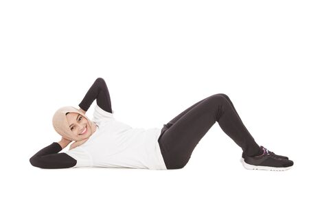 full body portrait of asian sporty woman doing sit up while smiling isolated on white background