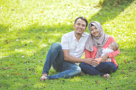 muslim baby girl: portrait of asian happy family with newborn baby in the park