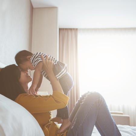 Porträt von Mutter und Baby spielen und lächelnd zu Hause.
