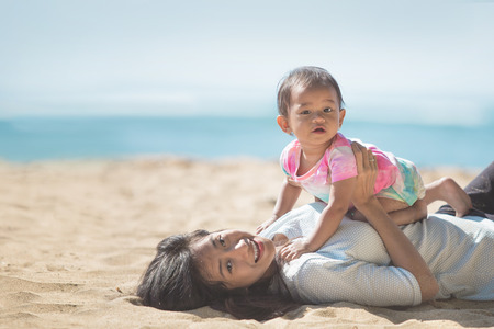 woman resting: portrait of Happy mother and baby girl playing at seaside