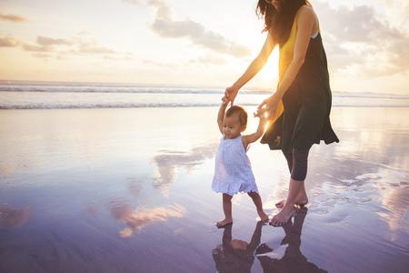 portret van een moeder die haar dochter onderwijst wandelingen op het strand