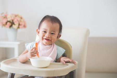 Retrato de feliz niña bebé sentado en la silla alta y alimentar a su auto Foto de archivo - 62206783