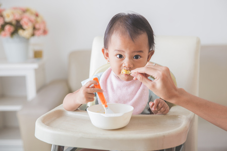 are fed: Portrait Of Happy Young Baby In High Chair being fed by mum Stock Photo