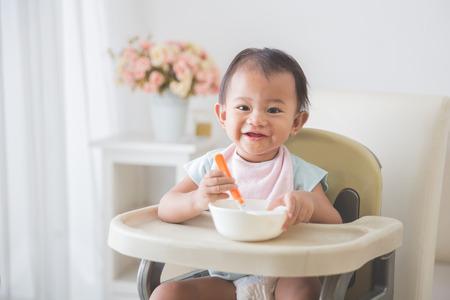 嬰兒: 快樂年輕的女嬰人像坐在高腳椅和餵她自我 版權商用圖片