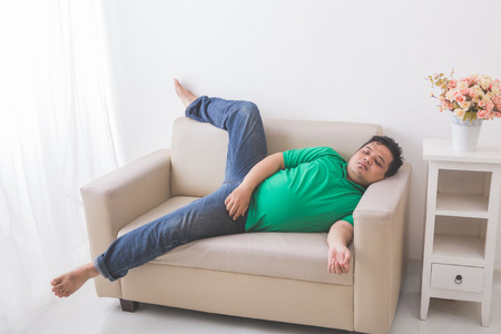 sprawl: portrait of lazy Fat obese man sleeping on the couch Stock Photo