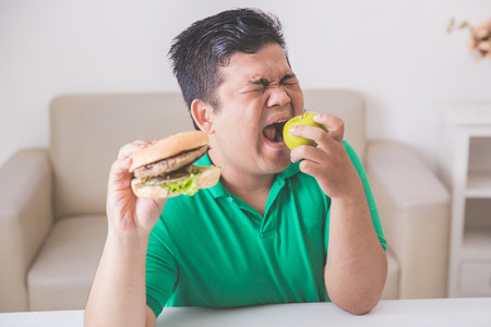 unhealthy lifestyle: man holding apple and hamburger in the other hand. healthy and unhealthy lifestyle concept Stock Photo