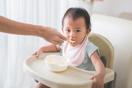 Portrait Of Happy Young Baby In High Chair being fed by mum Stock Photo