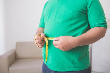 Retrato de cerca de hombre con sobrepeso midiendo su vientre en casa Foto de archivo