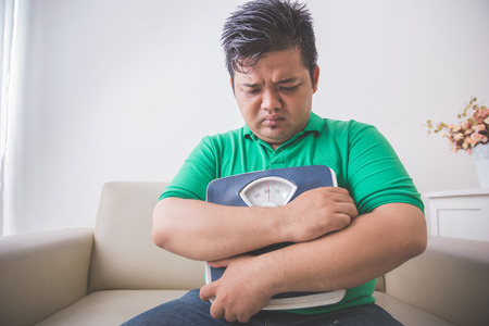 weight gain: Portrait of sad obese man holding a weight scale, thinking about his weight problem