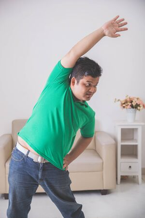 calisthenics: portrait of overweight man enjoy doing some exercise at home