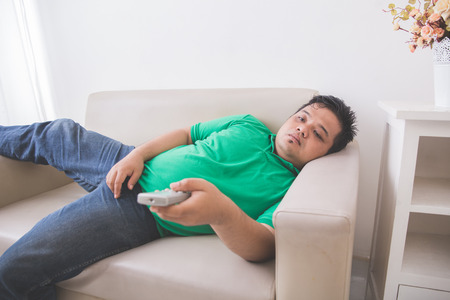 portrait of lazy Fat obese man laying on the couch and watching tv Imagens - 62207061
