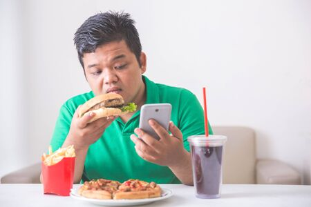fastfood: người đàn ông béo phì ăn trưa của ông rác hoặc thực phẩm không lành mạnh ở nhà trong khi sử dụng điện thoại di động
