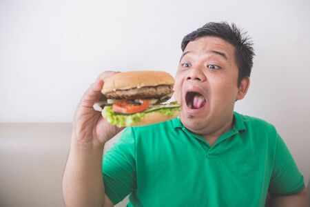 overweight man: Portrait of Overweight man eating hamburger at home