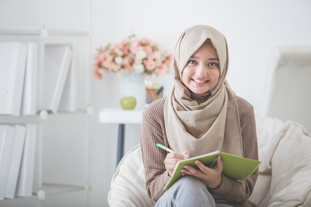 portrait of beautiful asian woman with head scarf writing something Stock Photo