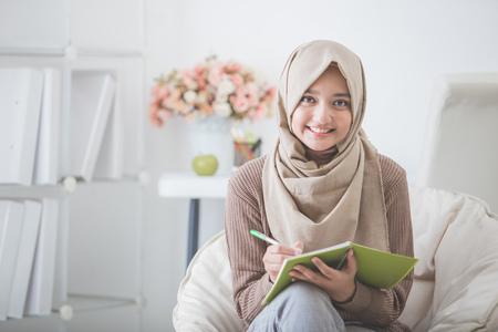 portret van mooie Aziatische vrouw met hoofddoek die iets schrijft
