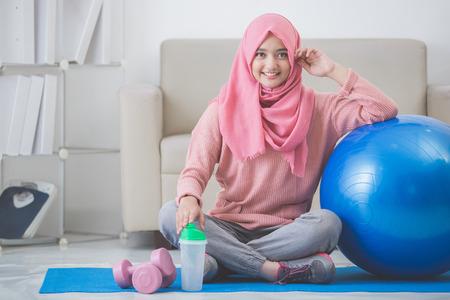 gezonde Aziatische moslim vrouw met hijab het doen van oefeningen thuis