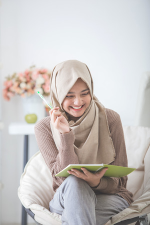 portrait of excited asian woman with hijab enjoy writing something