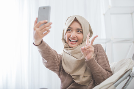 スマート フォンを使用して selfie を取ってヒジャーブを持つ女性の肖像画 写真素材