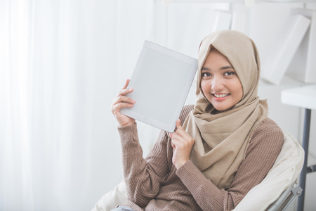 Online Business: portrait of woman showing and presenting tablet screen and smile to camera Stock Photo