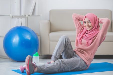 Sana mujer musulmana asiática de estiramiento mientras se hace ejercicio en el país Foto de archivo - 62622897