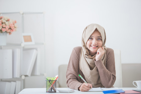 何かを書くヘッド スカーフで美しいアジアの女性の肖像画 写真素材