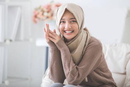 portret van aantrekkelijke jonge vrouw met hijab lacht naar de camera terwijl het zitten op de bank