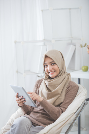 タブレット pc を使用して、リビング ルームに座っているヒジャーブを身に着けている現代のアジア女性