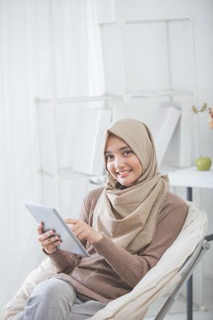 moderne Aziatische vrouw die hijab met behulp van tablet pc terwijl het zitten in een woonkamer