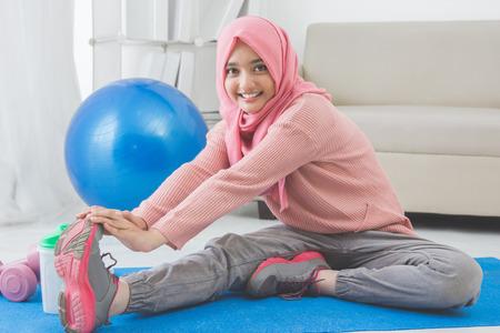 portret van gezonde Aziatische vrouw met hijab het doen van oefeningen thuis Stockfoto