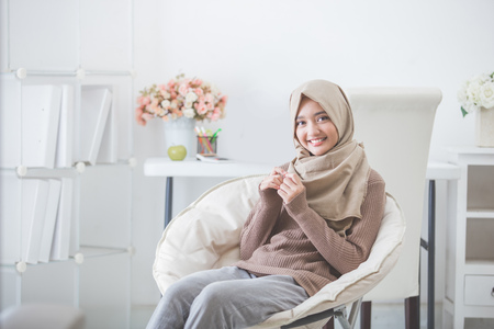 portrait of attractive young woman with hijab smiling to camera while sitting on couch