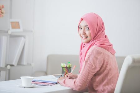 카메라에 웃는 hijab 입고 매력적인 아시아 여성 학생의 초상화 스톡 콘텐츠