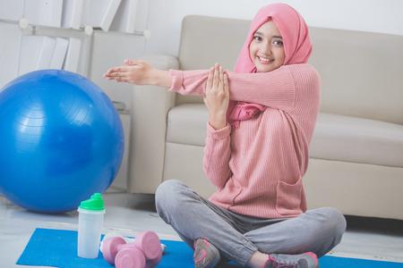 健康的なアジアのイスラム教徒の女性の家で運動をしながらストレッチ