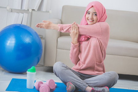 healthy asian muslim woman stretching while doing exercise at home Stock Photo