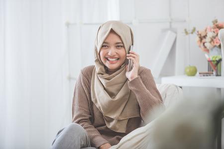 携帯電話で呼び出してヒジャーブを着て幸せなアジア女の肖像