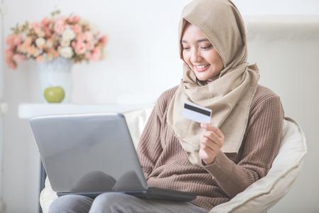 Retrato de mujer feliz que compra el producto a través de compras en línea. pagar con tarjeta de crédito Foto de archivo - 62622962