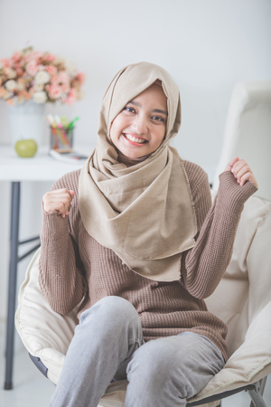 Retrato de mujer joven emocionada con hijab sonriendo mientras está sentado en un sofá Foto de archivo - 62622964