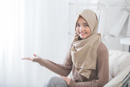 Retrato de una mujer joven y atractiva con el hijab sonriente que presenta a la copia espacio Foto de archivo - 62622966