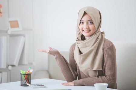 portret van aantrekkelijke jonge vrouw met hijab lacht presenteren aan de ruimte te kopiëren Stockfoto