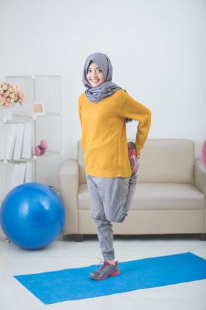 gezonde Aziatische moslim vrouw uitrekken terwijl het doen van oefeningen thuis