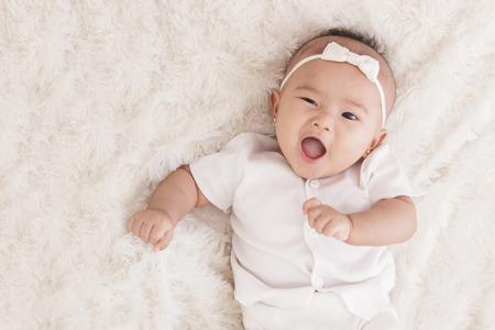 close up portrait adorable petite fille avec l'expression drôle couché sur couverture de fourrure avec copie espace