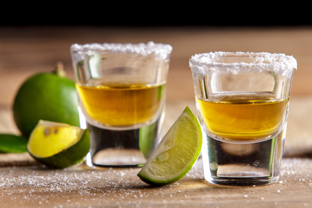 portrait of two tequila shots with lime slice and salt on wooden table