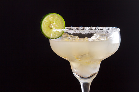 blended: close up portrait of fresh homemade margarita with lime and salt on black background with copy space