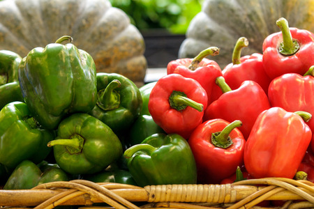 colfax: close up portrait of a group of fresh green and red bell peppers in a basket at supermarket