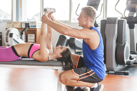 portrait of young woman workout lifting weights assisted by her trainer at the gym Stock Photo