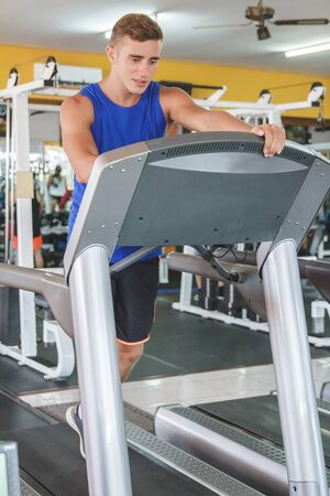 man gym: full body portrait of handsome sporty man on treadmill at the gym