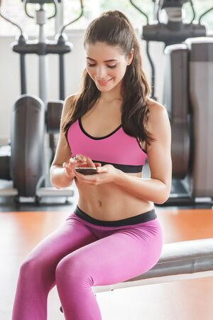 mobilephone: portrait of young man playing mobilephone while take a break during workout at the gym Stock Photo