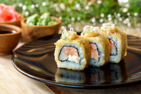 california roll: portrait of japanese cuisine california roll and tuna avocado roll on black plate served with wasabi and soy sauce Stock Photo