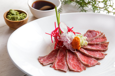portrait of japanese cuisine beef tataki on white plate